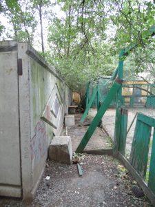 Бетонный забор почти вплотную граничит с разваливающейся хоккейной коробкой