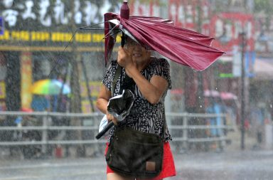 A woman holds her broken umbrella as she walks against strong wind and heavy rainfall as Typhoon Matmo hit Qingdao, Shandong province July 25, 2014. Matmo, which made landfall in Fujian Province on Wednesday, has brought strong winds and heavy downpours to more areas in China after it moved northward on Thursday, Xinhua News Agency reported. (Photo by Reuters/Stringer)