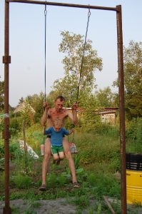На моём участке качеля - обычная досточка на двух верёвках, переброшенных через перекладину на двух столбах.