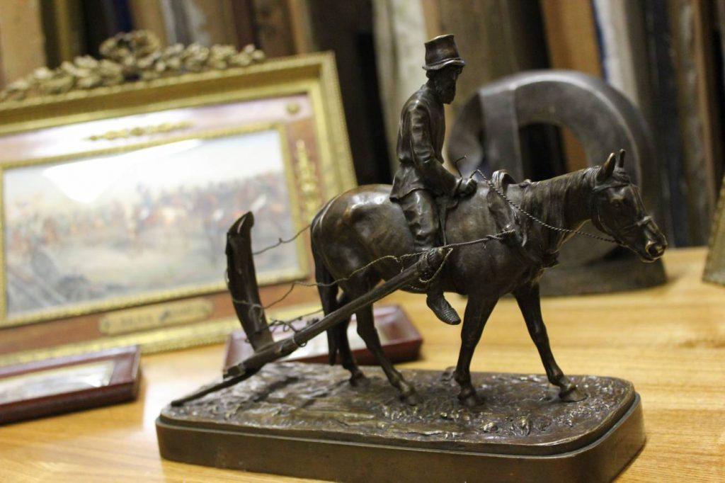 Вот крестьянин, который возвращается с пахоты. Бронзовая скульптура русского скульптора-анималиста Евгения Лансере. И здесь же работа неизвестного автора, которая тоже посвящена жизни простого человека. К основанию она прибита специальными гвоздями, таких уже и не делают.